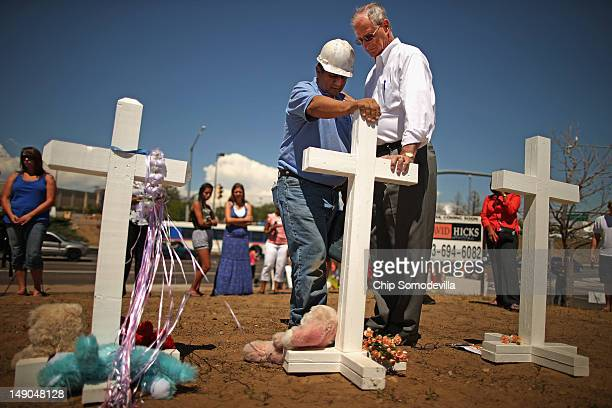 Greg Zanis of Aurora Illinois prays with Aurora Colorado Mayor Steve Hogan at the twelve crosses Zanis made for a makeshift memorial to the victims...