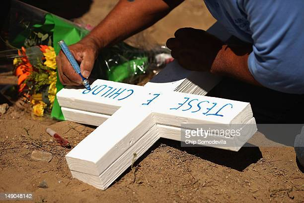 Greg Zanis of Aurora Illinois writes Jesse Childress' name on one of the twelve crosses he made for a makeshift memorial to the victims of last...