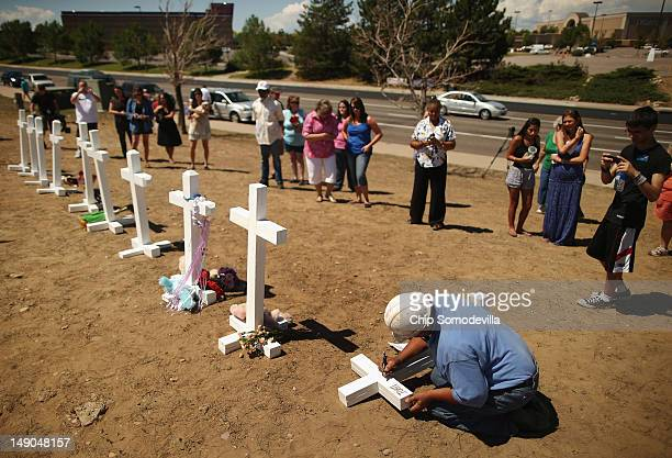 Greg Zanis of Aurora Illinois writes the names of the victims of last weekend's mass shooting on twelve crosses he made for a makeshift memorial...