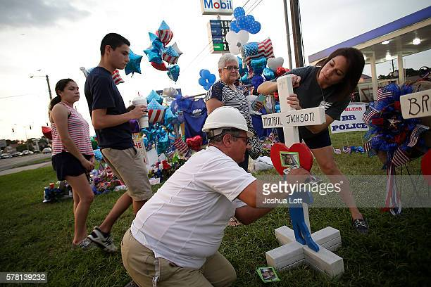 Greg Zanis staples a photo of Baton Rouge Police Officer Montrell Jackson to a cross he built as a woman tries a message at a makeshift memorial...