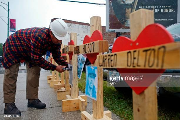 Greg Zanis staples a photograph to a wooden cross at a planned prayer vigil and rally against violence in Chicago Illinois on May 20 2017 Zanis makes...