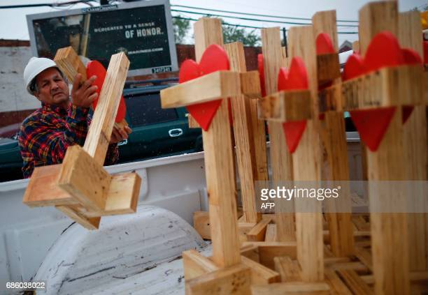 Greg Zanis unloads wooden crosses from the back of his truck at a planned prayer vigil and rally against violence in Chicago Illinois on May 20 2017...