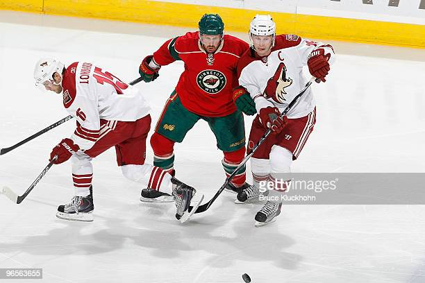 Greg Zanon of the Minnesota Wild battles for a loose puck with Matthew Lombardi and Shane Doan of the Phoenix Coyotes during the game at the Xcel...