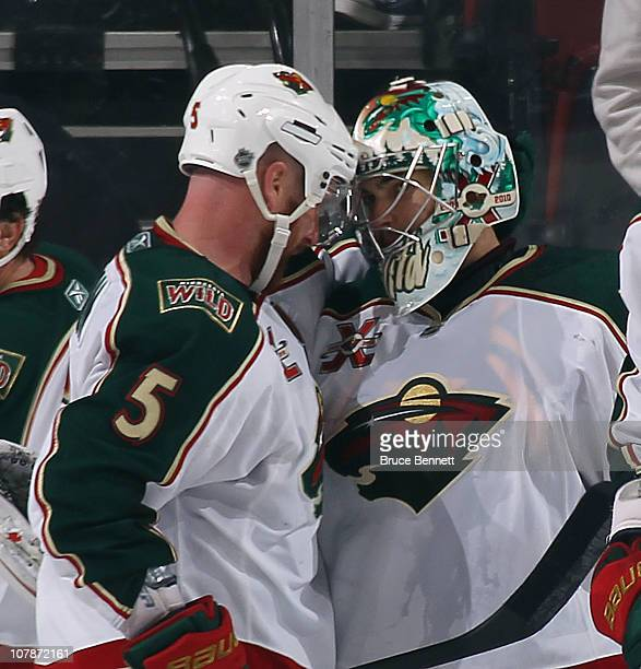 Greg Zanon of the Minnesota Wild congratulates teammate goalie Jose Theordore on his 21 win over the New Jersey Devils at the Prudential Center on...