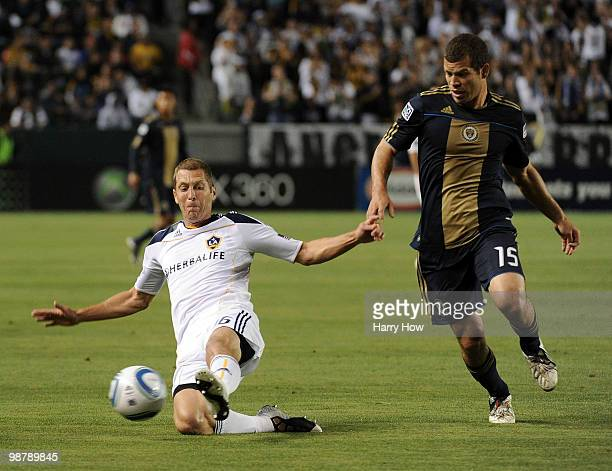 Gregg Berhalter of the Los Angeles Galaxy clears a ball in front of Alejandro Moreno of the Philadelphia Union during the first half at the Home...