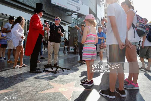 Gregg Donovan speaks with a reporter while holding a Trump 2020 sign as he stands near President Donald Trump's star on the Hollywood Walk of Fame on...