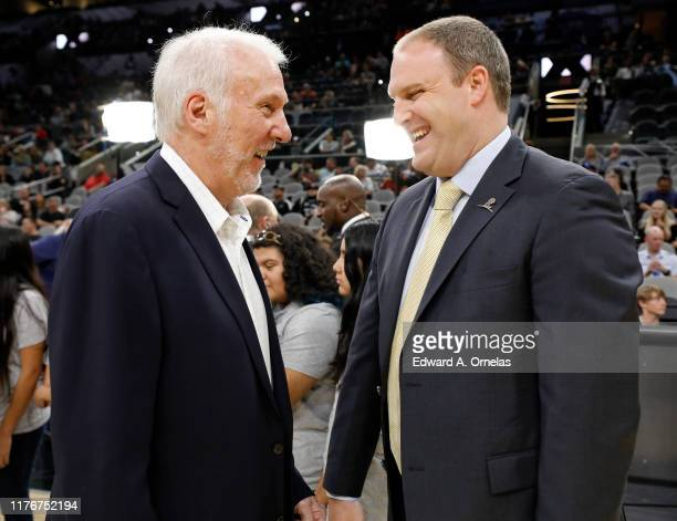 Gregg Popovich head coach of the San Antonio Spurs and Taylor Jenkins head coach of the Memphis Grizzlies talk before a preseason NBA game held at...
