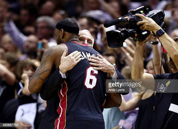 Gregg Popovich of the San Antonio Spurs hugs LeBron James of the Miami Heat at the end of Game Five of the 2014 NBA Finals at the ATT Center on June...
