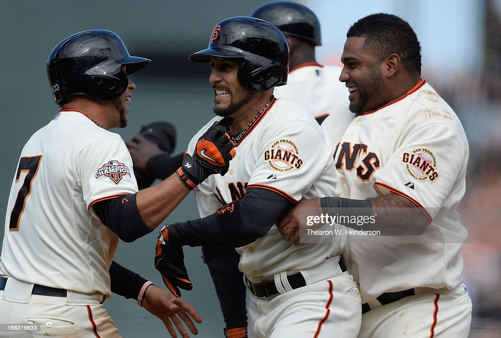 Gregor Blanco #7, Andres Torres #56, and Pablo Sandoval #48 of the San Francisco Giants celebrates after Torres hit an RBI walk-off single scoring Buster Posey #28 to defeat the Philadelphia Phillies 4-3 in the bottom of the 10th inning at AT&T Park on May 8, 2013 in San Francisco, California.