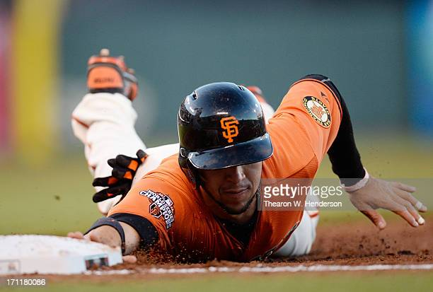 Gregor Blanco of the San Francisco Giants dives back into first base safe against the Miami Marlins at ATT Park on June 21 2013 in San Francisco...