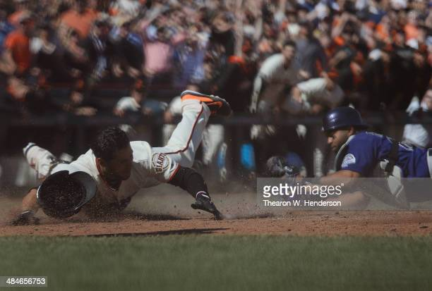Gregor Blanco of the San Francisco Giants is tagged out at the plate by Wilin Rosario of the Colorado Rockies attempting to stretch a triple into an...