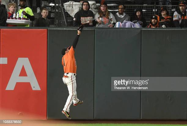 Gregor Blanco of the San Francisco Giants makes a leaping catch at the wall taking a hit away from Nolan Arenado of the Colorado Rockies in the top...