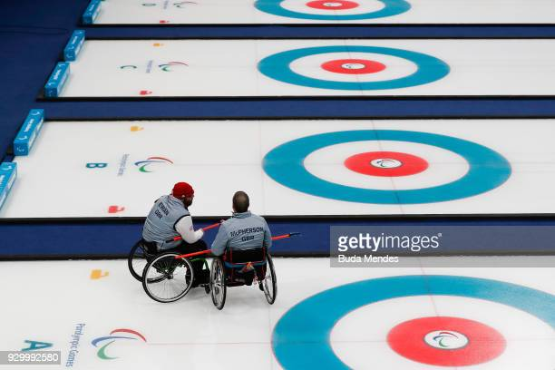 Gregor Ewan of Great Britain talks with his teammate Bob McPherson in the Wheelchair Curling Round Robin Session 01 during day one of the PyeongChang...