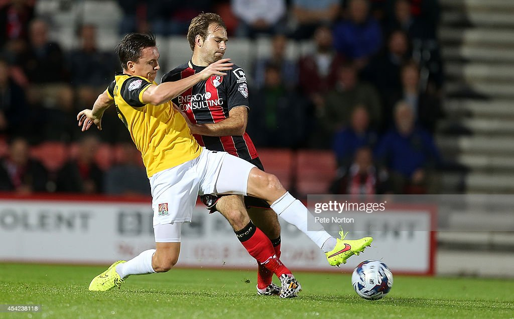 Gregor Robertson of Northampton Town contests the ball with Brett Pitman of AFC Bournemouth during the Capital One Cup Second Round match between AFC Bournemouth and Northampton Town at Goldsands Stadium on August 26, 2014 in Bournemouth, England.