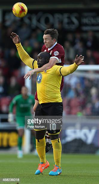 Gregor Robertson of Northampton Town rises above Adebayo Akinfenwa of AFC Wimbledon to head the ball during the Sky Bet League Two match between...