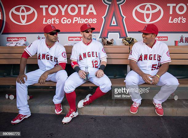 Gregorio Petit and Johnny Giavotella of the Los Angeles Angels of Anaheim pose while joking around in the dugout as Carlos Perez laughs before the...