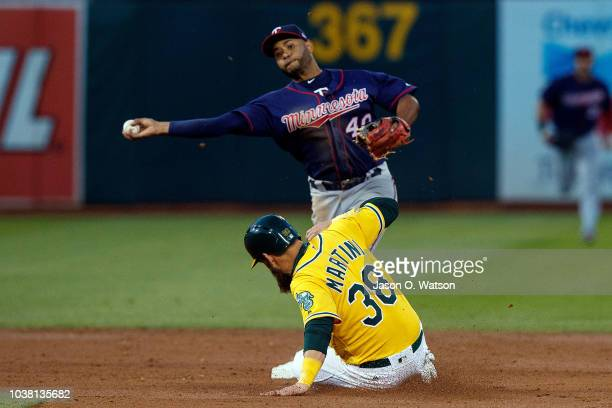 Gregorio Petit of the Minnesota Twins completes a double play over Nick Martini of the Oakland Athletics during the third inning at the Oakland...