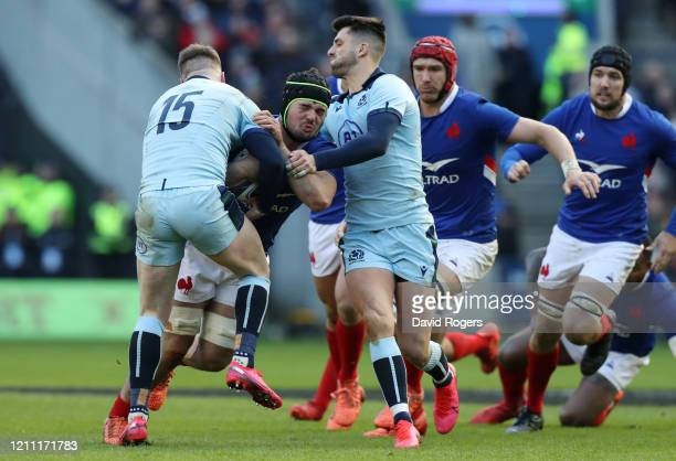 Gregory Alldritt of France is tackled by Stuart Hogg of Scotland and Adam Hastings of Scotland during the 2020 Guinness Six Nations match between...