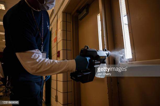 Gregory Bass, a member of Jefferson County Public Schools housekeeping staff, sanitizes an exterior door to display COVID-19 safety precautions at...