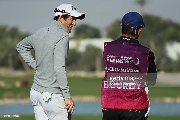 Gregory Bourdy of France chats with his caddie on the 15th green during the second round of the Commercial Bank Qatar Masters at the Doha Golf Club...