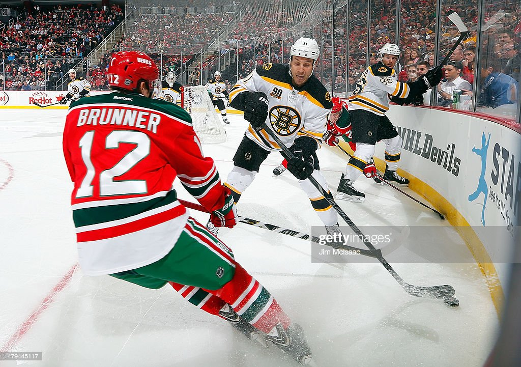 Gregory Campbell #11 of the Boston Bruins clears the puck against Damien Brunner #12 of the New Jersey Devils at the Prudential Center on March 18, 2014 in Newark, New Jersey.