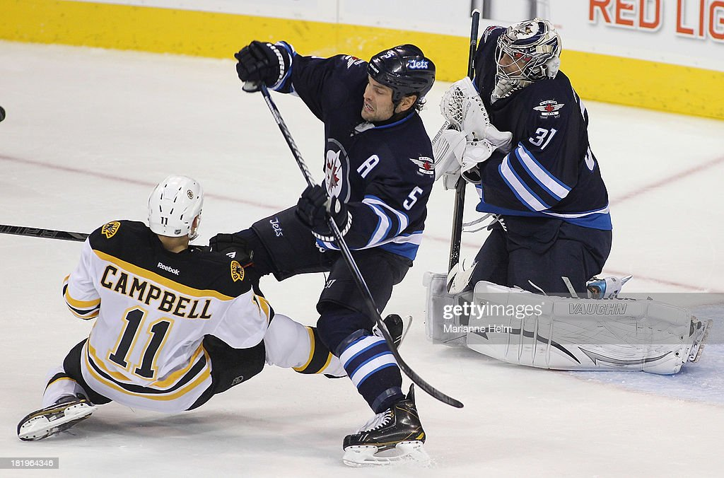 Gregory Campbell #11 of the Boston Bruins collides with Mark Stuart #5 of the Winnipeg Jets in front of goaltender Ondrej Pavelev #31 in third period action during an NHL preseason game at the MTS Centre on September 26, 2013 in Winnipeg, Manitoba, Canada.