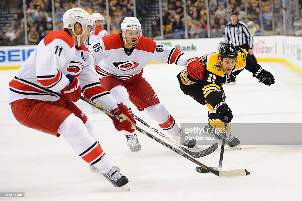 Gregory Campbell #11 of the Boston Bruins reaches for the puck against Jordan Staal #11 and Ron Hainsey #65 of the Carolina Hurricanes at the TD Garden on November 23, 2013 in Boston, Massachusetts.