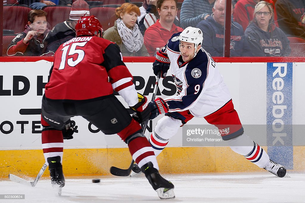 Gregory Campbell #9 of the Columbus Blue Jackets passes the puck against Boyd Gordon #15 of the Arizona Coyotes during the NHL game at Gila River Arena on December 17, 2015 in Glendale, Arizona. The Blue Jackets defeated the Coyotes 7-5.