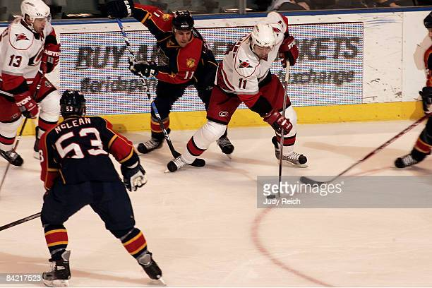 Gregory Campbell of the Florida Panthers and Justin Williams of the Carolina Hurricanes battle for possession of the puckat the Bank Atlantic Center...