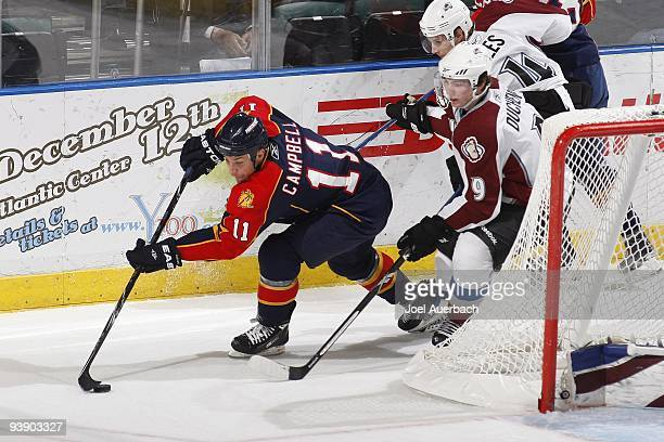 Gregory Campbell of the Florida Panthers attempts to center the puck while being defended by Matt Duchene of the Colorado Avalanche on December 2...
