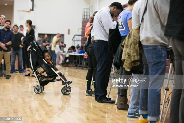 Gregory Jones waits as his mother and other voters cast their ballots at a polling station set up at Grady High School for the midterm elections on...