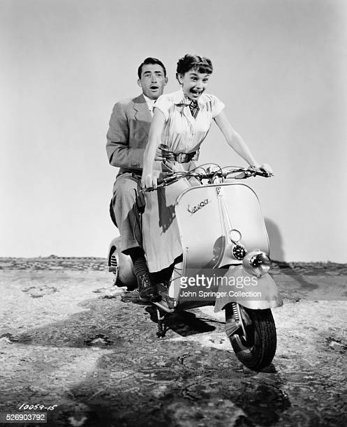 Gregory Peck and Audrey Hepburn practice a moped scene for the 1953 comedic romance Roman Holiday in which Peck plays the role of journalist Joe...