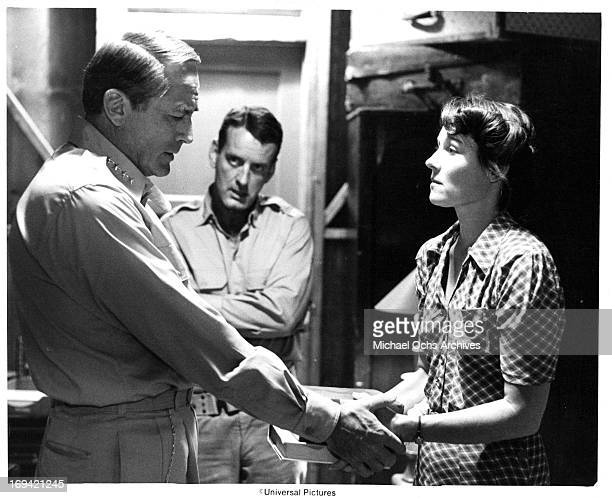 Gregory Peck holding the hands of Marj Dusay as Nicolas Coster watches in a scene from the film 'MacArthur' 1977