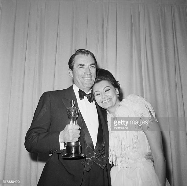 Gregory Peck holds his Academy Award for Best Actor while Sophia Loren puts her head on this shoulder Loren had presented the Best Actor Oscar as she...