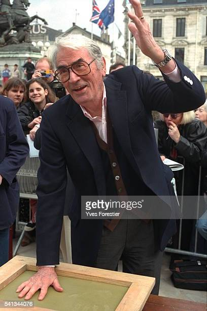 Gregory Peck makes hand prints in wet cement at the 14th Detective Film Festival in Cognac France