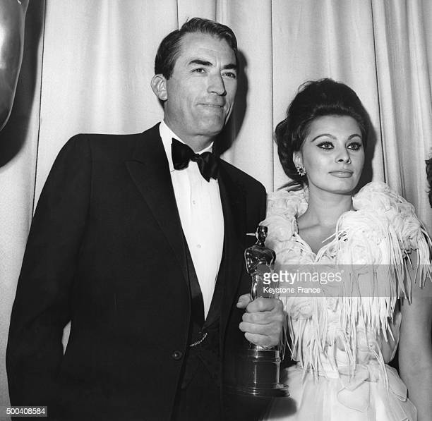 Gregory Peck poses with Italian actress Sophia Loren after he won the award as best actor for his performance in the movie 'To Kill a Mockingbird'...