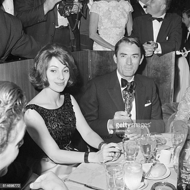Gregory Peck sits with his wife Veronique and the Oscar he just won for Best Actor in To Kill a Mockingbird at the Academy Awards.