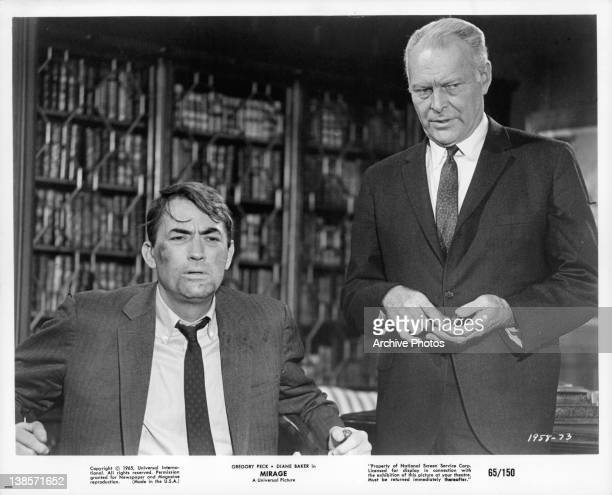 Gregory Peck sitting looking disheveled in a suit an unknown actor is standing behind him in a scene from the film 'Mirage' 1965
