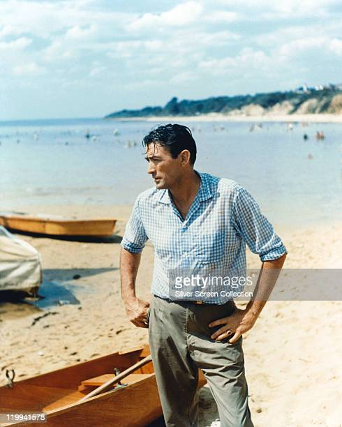 Gregory Peck , US actor, poses on a beach, with various small boats in the background, circa 1958.