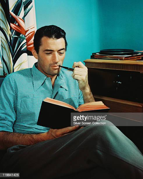 Gregory Peck , US actor, smoking a pipe while reading a book, while listening to records playing on a turntable beside him, circa 1955.