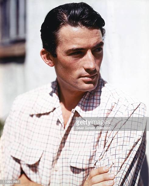 Gregory Peck US actor wearing a light check shirt as he looks to his left circa 1950