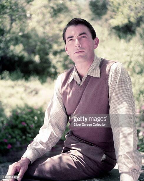 Gregory Peck , US actor, wearing a tank top over in a shirt as he relaxes in a clearing, wth light shining through beyond, circa 1950.