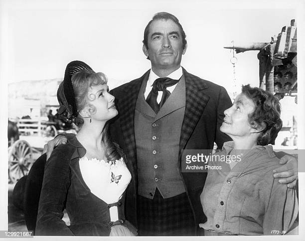 Gregory Peck with his arms around Debbie Reynolds and unidentified woman in a scene from the film 'How The West Was Won' 1962