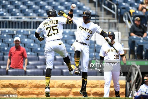 Gregory Polanco of the Pittsburgh Pirates celebrates his solo home run with Erik Gonzalez during the fourth inning against the Chicago Cubs at PNC...
