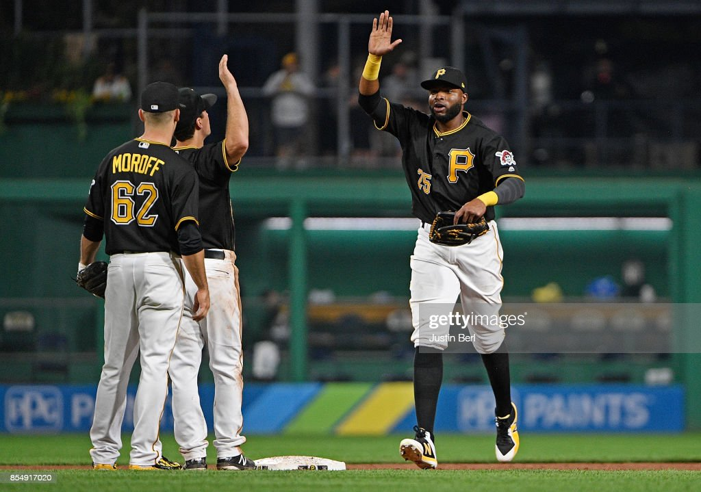 Gregory Polanco #25 of the Pittsburgh Pirates celebrates with Adam Frazier #26 and Max Moroff #62 after the final out in the Pittsburgh Pirates 5-3 win over the Baltimore Orioles at PNC Park on September 27, 2017 in Pittsburgh, Pennsylvania.