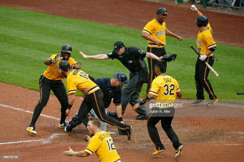 Gregory Polanco #25 of the Pittsburgh Pirates celebrates with Colin Moran #19 after sliding in safe to win the game in the tenth inning against the Milwaukee Brewers at PNC Park on July 15, 2018 in Pittsburgh, Pennsylvania.