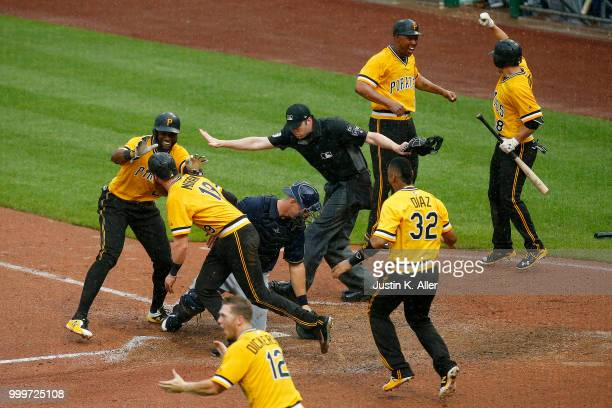 Gregory Polanco of the Pittsburgh Pirates celebrates with Colin Moran after sliding in safe to win the game in the tenth inning against the Milwaukee...