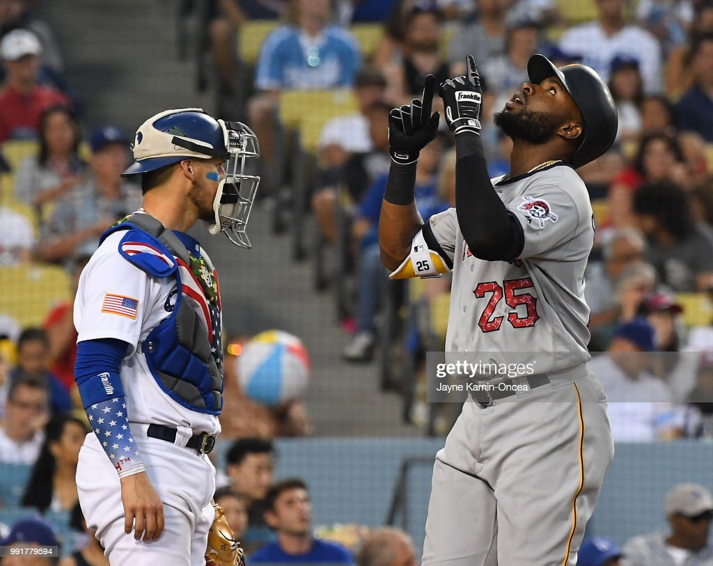 Gregory Polanco #25 of the Pittsburgh Pirates crosses home plate on his two-run home run as Yasmani Grandal #9 of the Los Angeles Dodgers looks on in the eighth inning of the game at Dodger Stadium on July 4, 2018 in Los Angeles, California.