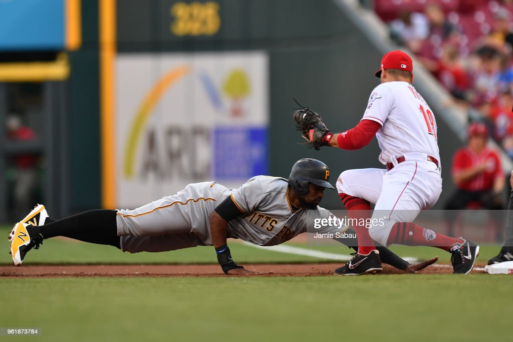 Gregory Polanco #25 of the Pittsburgh Pirates dives back to first base to avoid a pickoff from Joey Votto #19 of the Cincinnati Reds in the first inning at Great American Ball Park on May 23, 2018 in Cincinnati, Ohio.