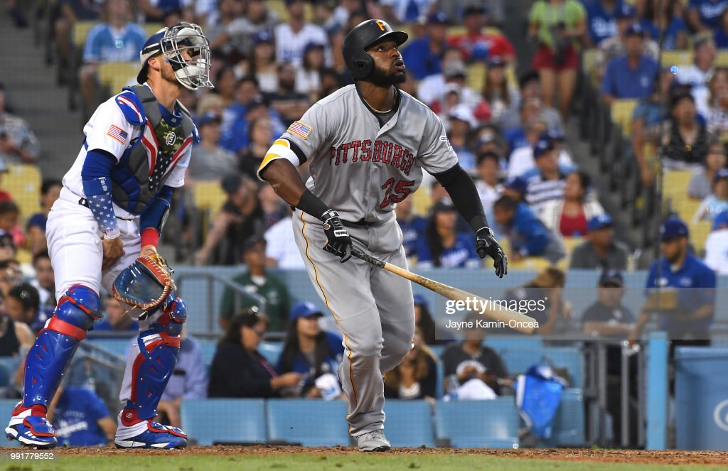 Gregory Polanco #25 of the Pittsburgh Pirates hits a two-run home run as Yasmani Grandal #9 of the Los Angeles Dodgers looks on in the eighth inning of the game at Dodger Stadium on July 4, 2018 in Los Angeles, California.